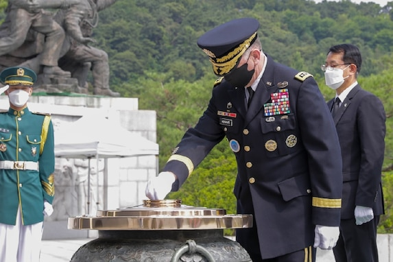 """Gen. Robert B. """"Abe"""" Abrams offers incense for fallen and missing soldiers in front of the memorial tower at the Seoul National Cemetery in Seoul."""