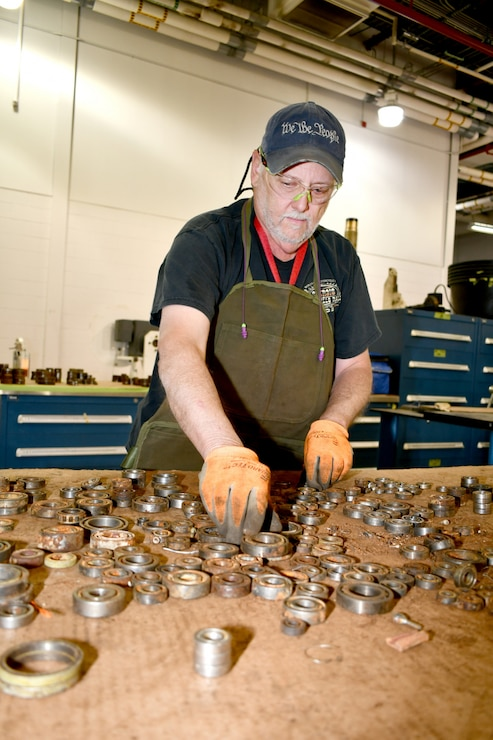 Wesley Mason, FRCE test cell operator, sorts scrap aircraft bearings to prepare them for demilitarization and disposal. Identifying, sorting and tagging scrap aircraft parts can be an expensive, time-consuming process. FRCE has joined a partnership with GE Aviation to simplify the scrapping process for T64 and F404 engine parts.