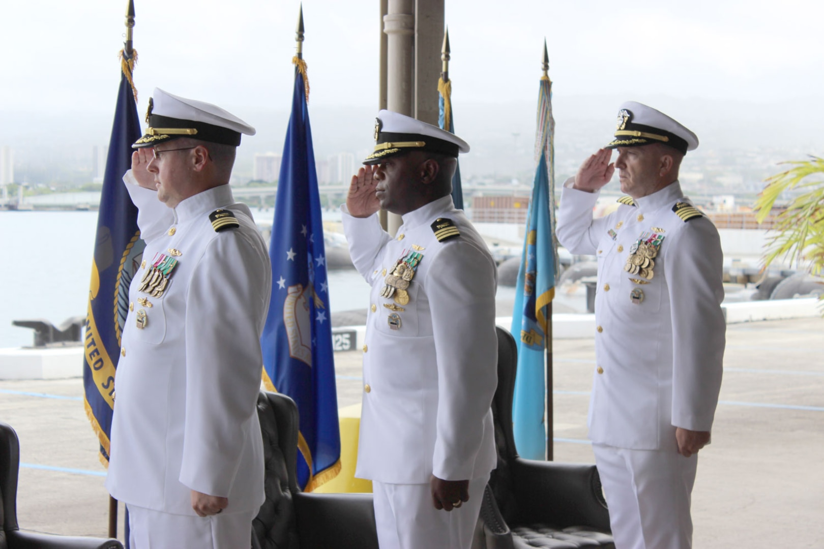 Three Navy officers salute