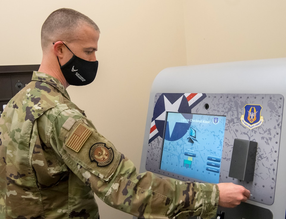 Master Sgt. Joshua Sandefur, 434th Communications Squadron client systems technician, demonstrates how to sign out a Google Chromebook from one of the many kiosks available to Grissom Airmen on March 13, 2021, Grissom Air Reserve Base, Indiana. Airmen can use the laptops to access the Air Force network safely and securely from home. (U.S. Air Force photo by Senior Airman Jonathan Stefanko)