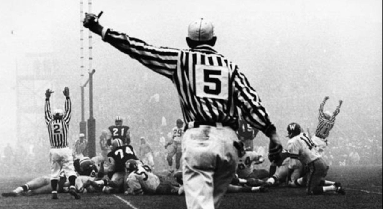 A team makes touchdown as a referee moves toward the action on a foggy field.