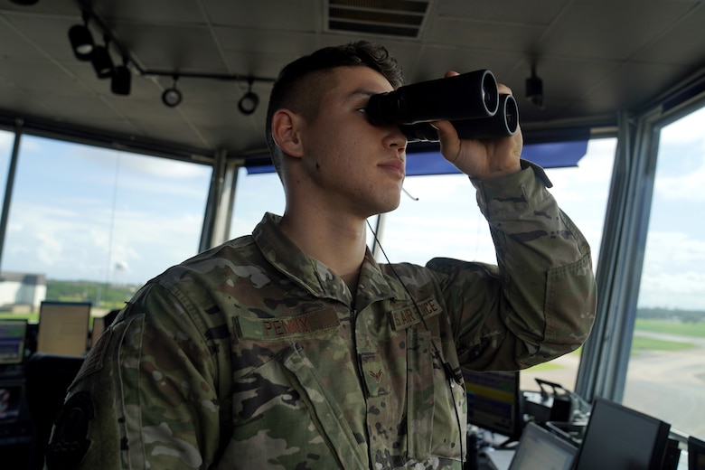 U.S. Air Force Airman 1st Class Jacob Penny, 81st Training Wing air traffic controller, poses for a photo with binoculars inside the Keesler Air Traffic Control tower at Keesler Air Force Base, Mississippi, June 25, 2021. The 81st TRW Operations Support Flight traffics the aircraft on the Keesler flightline and the local airspace. (U.S. Air Force photo by Senior Airman Seth Haddix)
