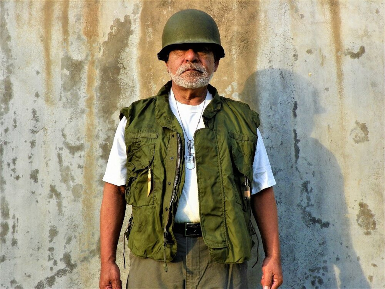 A man in a military helmet and vest stands for a photo.