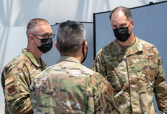 Chief Master Sgt. Timothy Bayes, left, 436th Airlift Wing command chief and Col. Matt Husemann, right, 436th AW commander, speak with Capt. Samuel Chavez, Patriot Express COVID-19 testing site officer in charge, at the Baltimore/Washington International Thurgood Marshall Airport in Baltimore, June 27, 2021. The facility, operated by Team Dover and other Air Mobility Command Airmen since November 2020, provides on-site, rapid COVID-19 testing for individuals traveling to overseas duty locations. (U.S. Air Force photo by Airman 1st Class Cydney Lee)