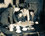 Jedburghs get instructions from Briefing Officer in London,  England, ca. 1944. (Office of Strategic Services/U.S. National Archives and Records Administration)