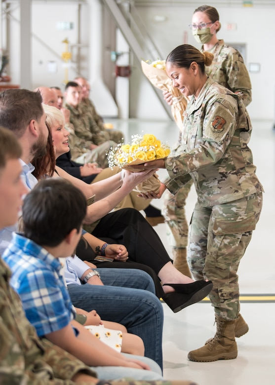 Tech. Sgt. Alicia Williams, a recruiter with the Kentucky Air National Guard, presents a bouquet of roses to the wife of Chief Master Sgt. James Tongate, the incoming state command chief, at his assumption-of-responsibility ceremony at the Kentucky Air National Guard Base in Louisville, Ky., May 15, 2021. (U.S. Air National Guard photo by Senior Airman Chloe Ochs)