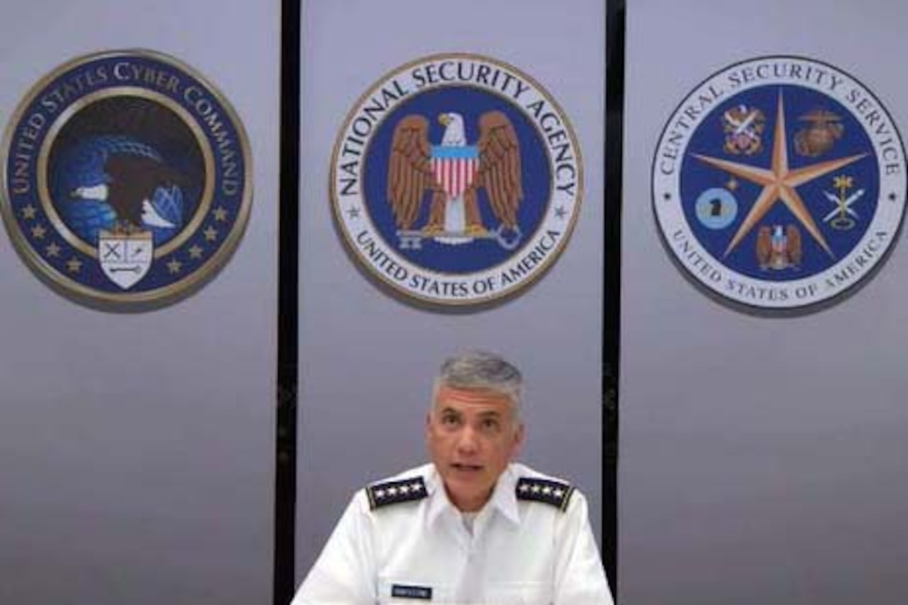 A man wearing a uniform sits and looks into a camera and speaks. Three large emblems are on the wall behind him.