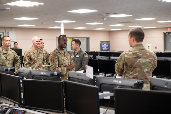 U.S. Air Force Col. Travis Edwards, center, 621st Contingency Response Wing commander, receives a unit briefing from members of the 621 st Mobility Support Operations Squadron during his East Coast immersion June 25, 2021, at Joint Base McGuire-Dix-Lakehurst, New Jersey. Edwards participated in an immersion event, centered around a simulated contingency scenario and learned what each squadron would provide if that contingency happened. (U.S. Air Force photo by Tech. Sgt. Luther Mitchell)