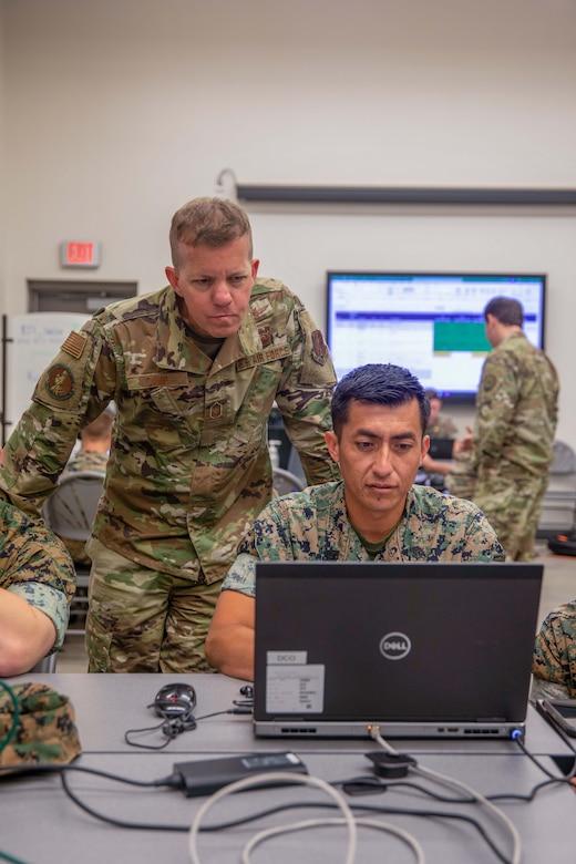 Troops work on laptops.