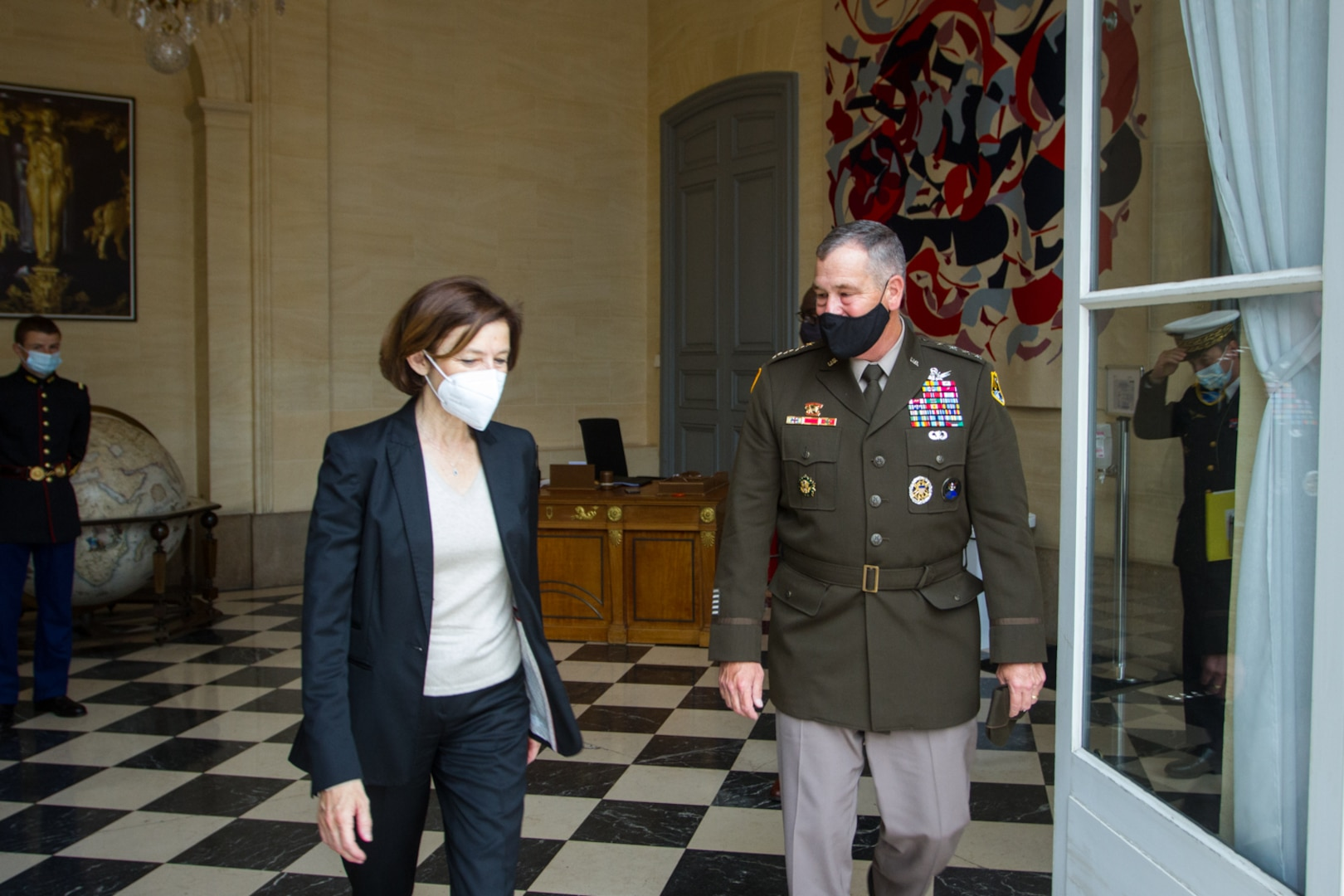 French defense minister and U.S. Army general walk.
