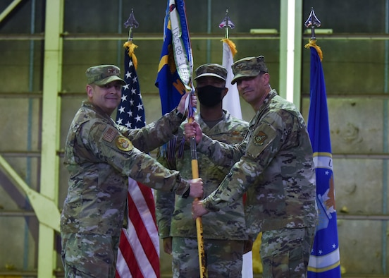 Two military members hold a guidon looking into the camera in front of another military member.
