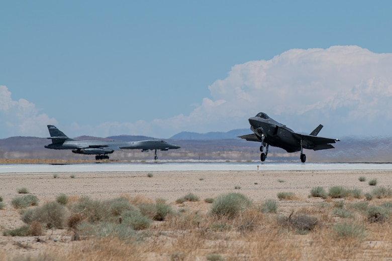 F-35 prepares to take off as a B-1 taxis on the runway behind it