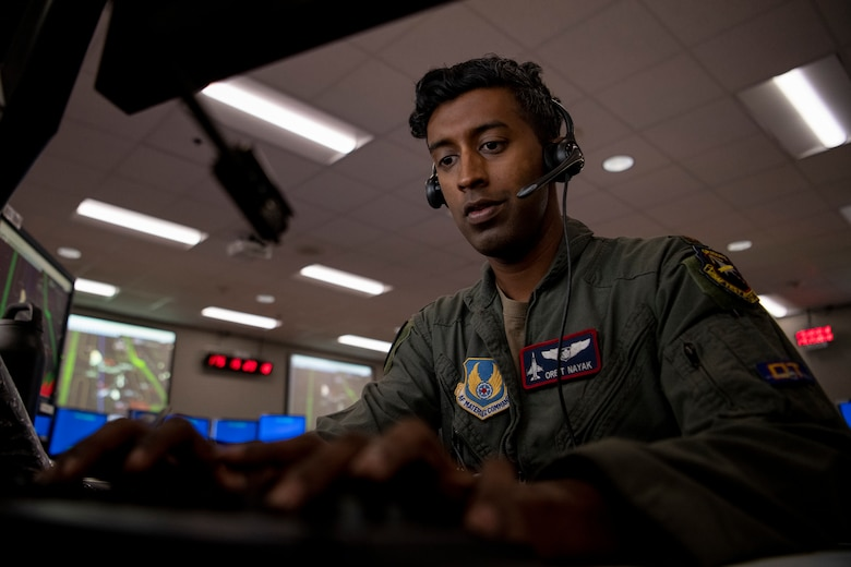 Airman works on computer with headset