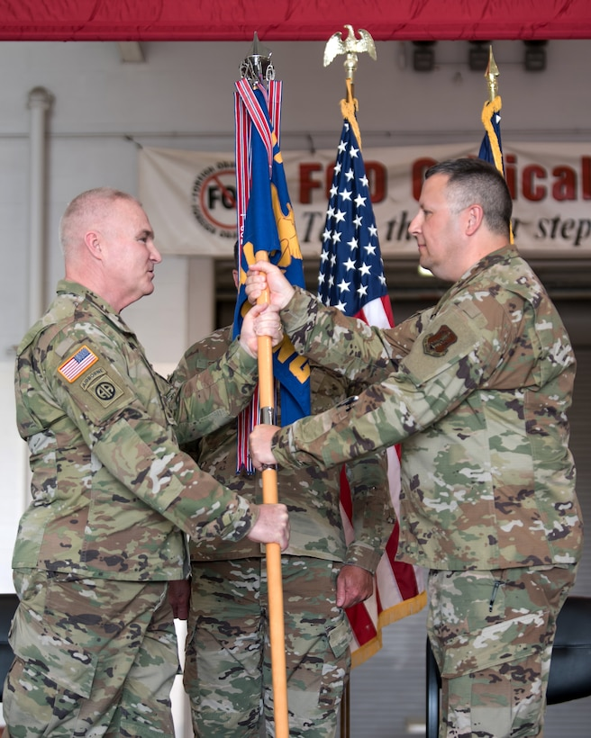 Chief Master Sgt. James Tongate (right), incoming state command chief of the Kentucky Air National Guard, accepts the Joint Forces Headquarters—Air guidon from Brig. Gen. Hal Lamberton (left), adjutant general of Kentucky, during a ceremony at the Kentucky Air National Guard Base in Louisville, Ky., May 15, 2021. Tongate previously served as the 123rd Airlift Wing's human resource advisor. (U.S. Air National Guard photo by Senior Airman Chloe Ochs)