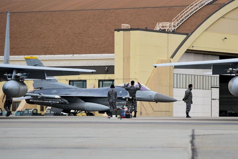 """An aircraft maintenance crew member with the Koku Jietai (Japan Air Self Defense Force) strikes the 80th Fighter Squadron """"crush em"""" pose as an F-16 Fighting Falcon assigned to Kunsan Air Base, Republic of Korea, taxis by  during Red Flag-Alaska 21-2 at Eielson Air Force Base, Alaska, June 18, 2021. RF-A is a U.S. Pacific Air Forces-sponsored exercise designed to provide training to U.S. and allied forces in a simulated combat environment. (U.S. Air Force photo by Senior Airman Suzie Plotnikov)"""