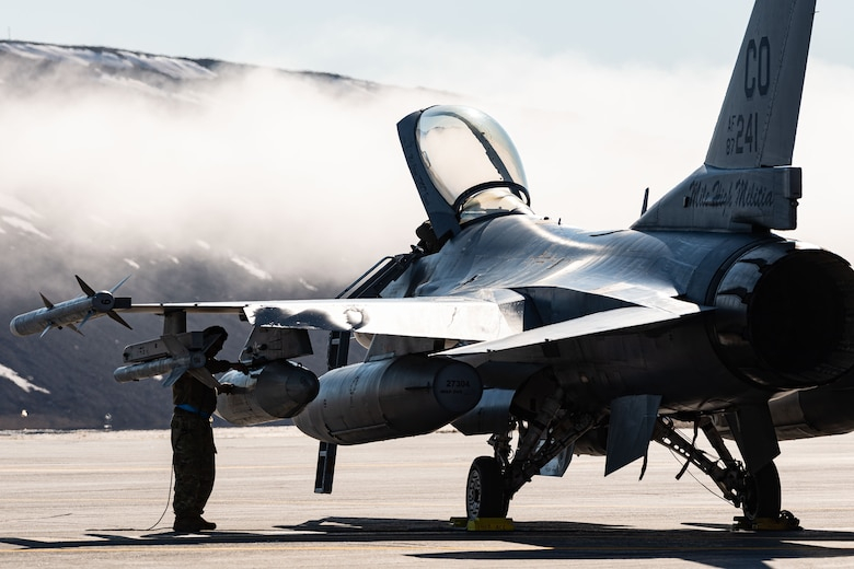 A United States Air Force aircraft maintenance technician conducts post flight inspection of a United States Air Force F-16 Fighting Falcon fighter jet during Exercise Amalgam Dart at Thule Air Base, Greenland, June 12, 2021.