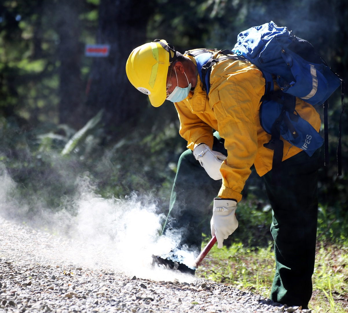Washington National Guard Pfc. Xavier Cha, 1st Battalion, 161st Infantry Regiment, practices with a flare during wildfire training with the Washington Department of Natural Resources June 24, 2021, in Rainier, Wash. About 250 Washington National Guard members received firefighter training this spring in preparation for wildfire season.