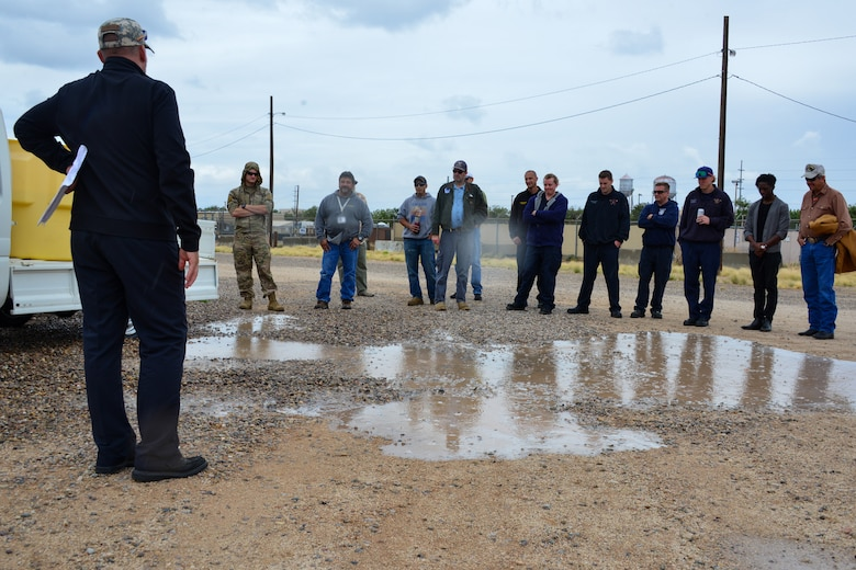 Man demonstrates what a 55 gallon spill looks like to a small group of people at Kirtland, AFB.