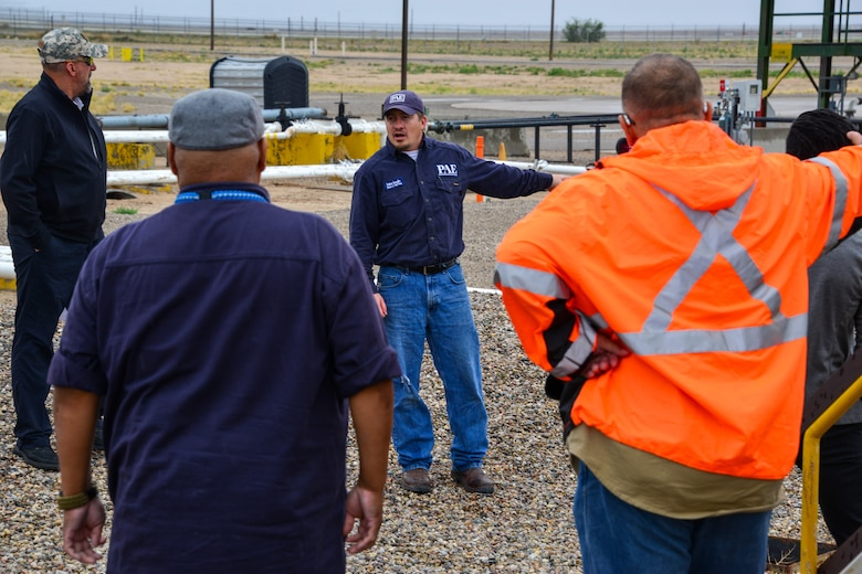 Man explains spill prevention protocol to a small group of people at Kirtland, AFB.