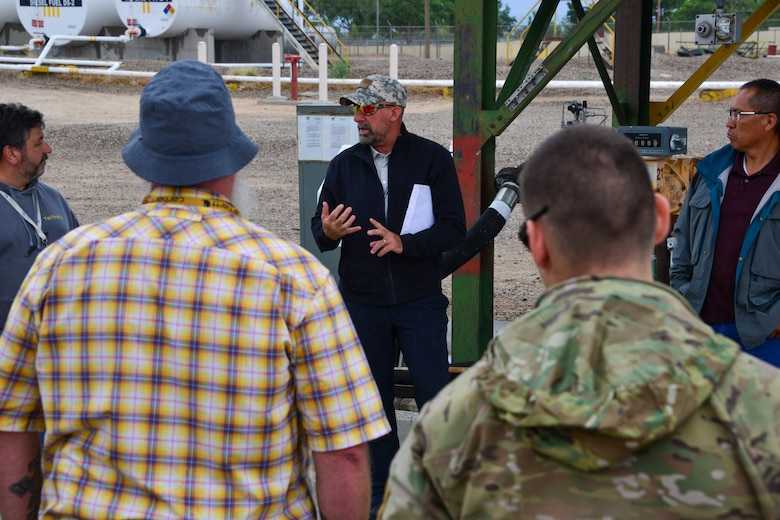 Man explaining spill prevention to a small group of people at Kirtland, AFB.