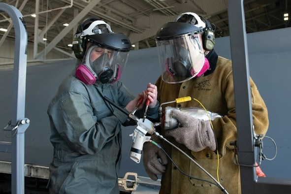 Staff Sgt. Chynna Patterson, a 28th Maintenance Group additive manufacturing spray technician, and David Darling, the 28th MXG additive manufacturing site manager, performs a cold spray restoration at Ellsworth Air Force Base, S.D., May 12, 2021.