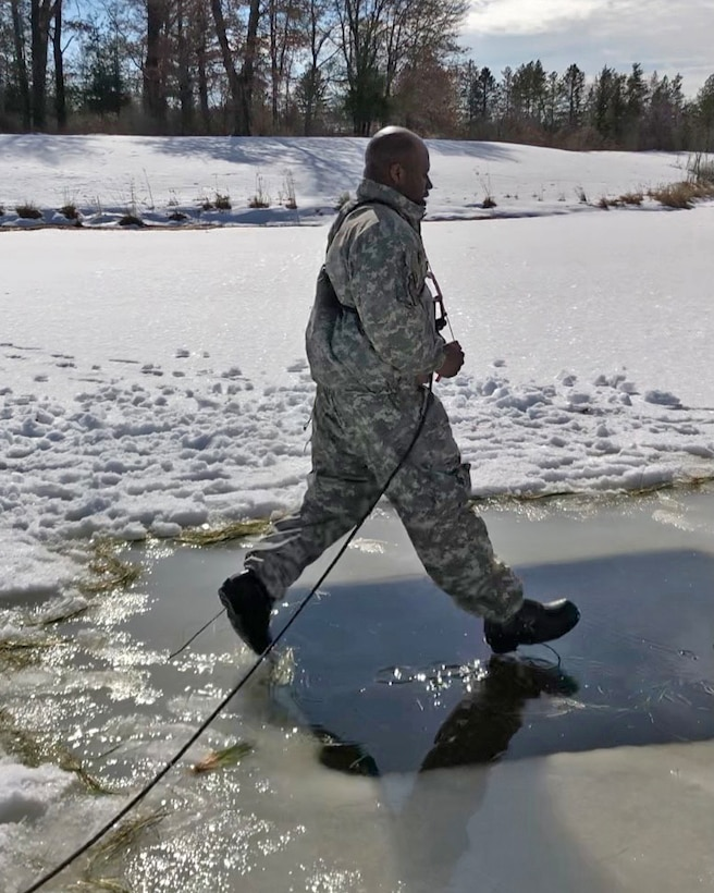 Staff Sgt. Rashad Wilson jumps into freezing water at U.S. Army's Cold Weather Operations Course.