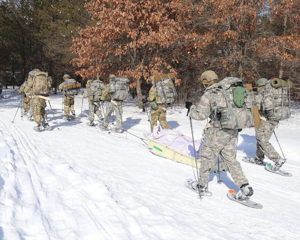 Airmen pulling ahkio sled at U.S. Army Cold Weather Operations Course.