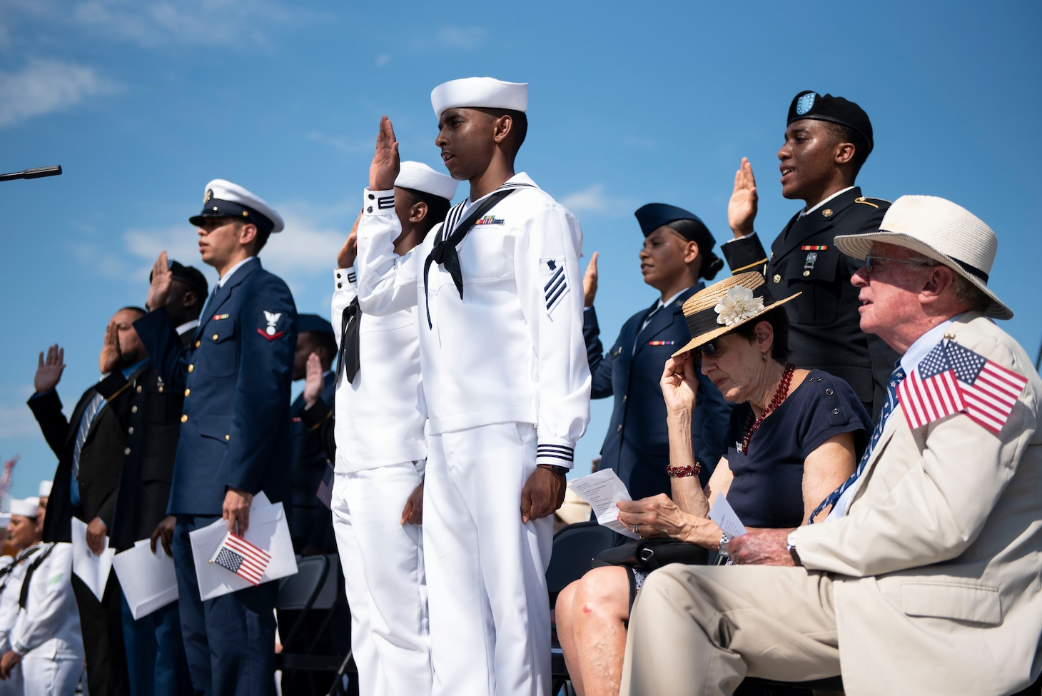 Soldiers, Sailors, Airmen, a Coast Guardsman and an Army veteran raise their right hands as they recite the Oath of Allegiance during a naturalization ceremony aboard USS Constitution.