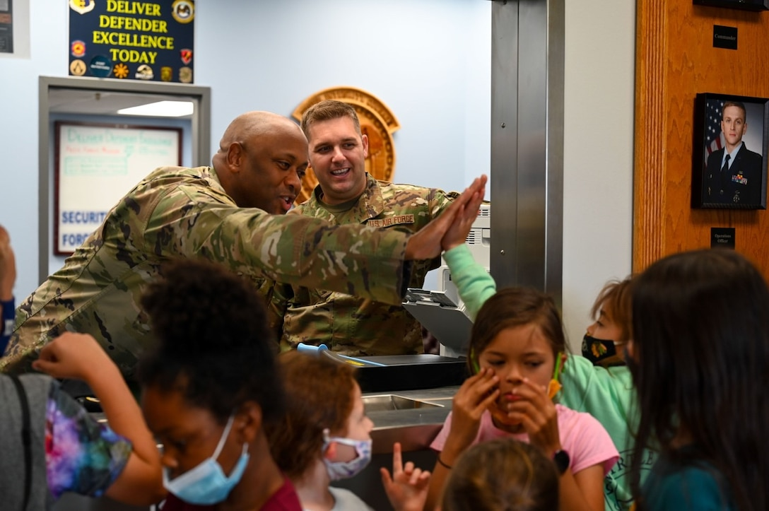 Lt. Col. David Herndon, the 28th Security Forces Squadron commander, gives a high five to one of the children enrolled in the School Age Care program at Ellsworth Air Force Base, S.D., June 25, 2021.