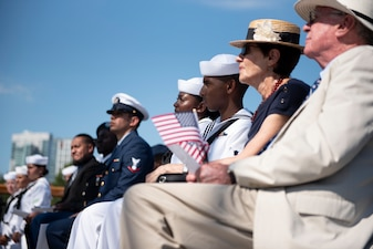 Soldiers, Sailors, Airmen, a Coast Guardsman and an Army veteran, and their guests, listen to remarks during a naturalization ceremony aboard USS Constitution.