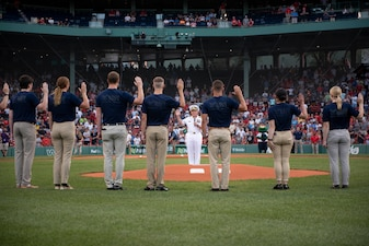 Chief of Naval Operations Adm. Mike Gilday administers the oath of enlistment to future U.S. Navy Sailors prior to a Red Sox baseball game at Fenway Park, Boston.