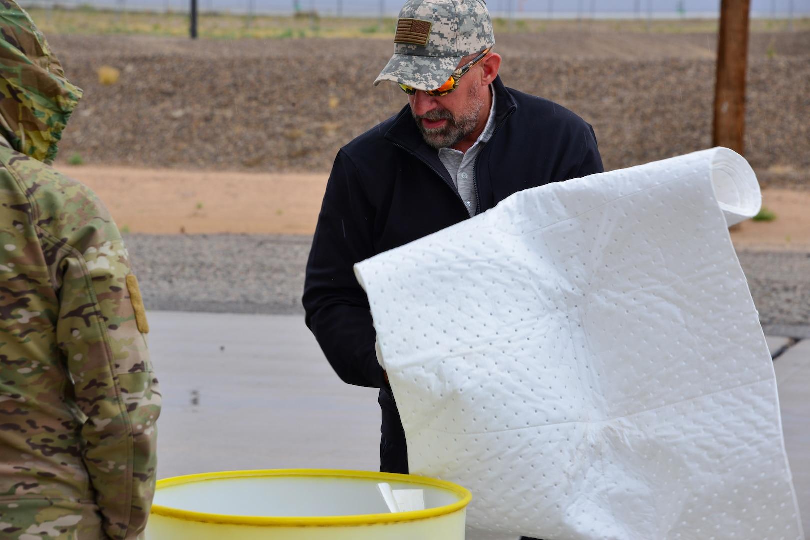 Man holds spill kit absorbent blanket at Kirtland, AFB.