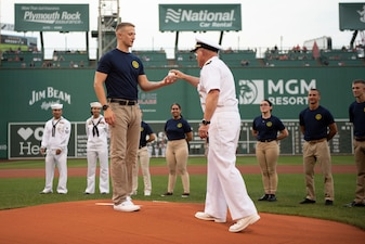 Chief of Naval Operations Adm. Mike Gilday hands the first pitch to a newly-enlisted Navy Sailor to throw at a Red Sox baseball game at Fenway Park, Boston.