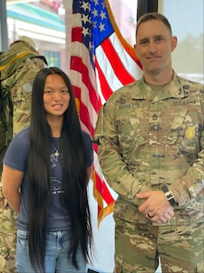 photo of a young lady and a man in uniform.