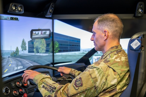 Col. Matt Husemann, 436th Airlift Wing commander, operates a 550Truckplus driving simulator at Dover Air Force Base, Delaware, June 22, 2021. The simulator immerses drivers in various weather conditions, vehicles, road conditions and equipment malfunctions to produce a safe, well-rounded training environment. (U.S. Air Force photo by Airman 1st Class Cydney Lee)