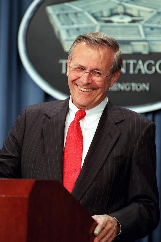 Defense Secretary Donald H. Rumsfeld smiles while standing at a lectern.