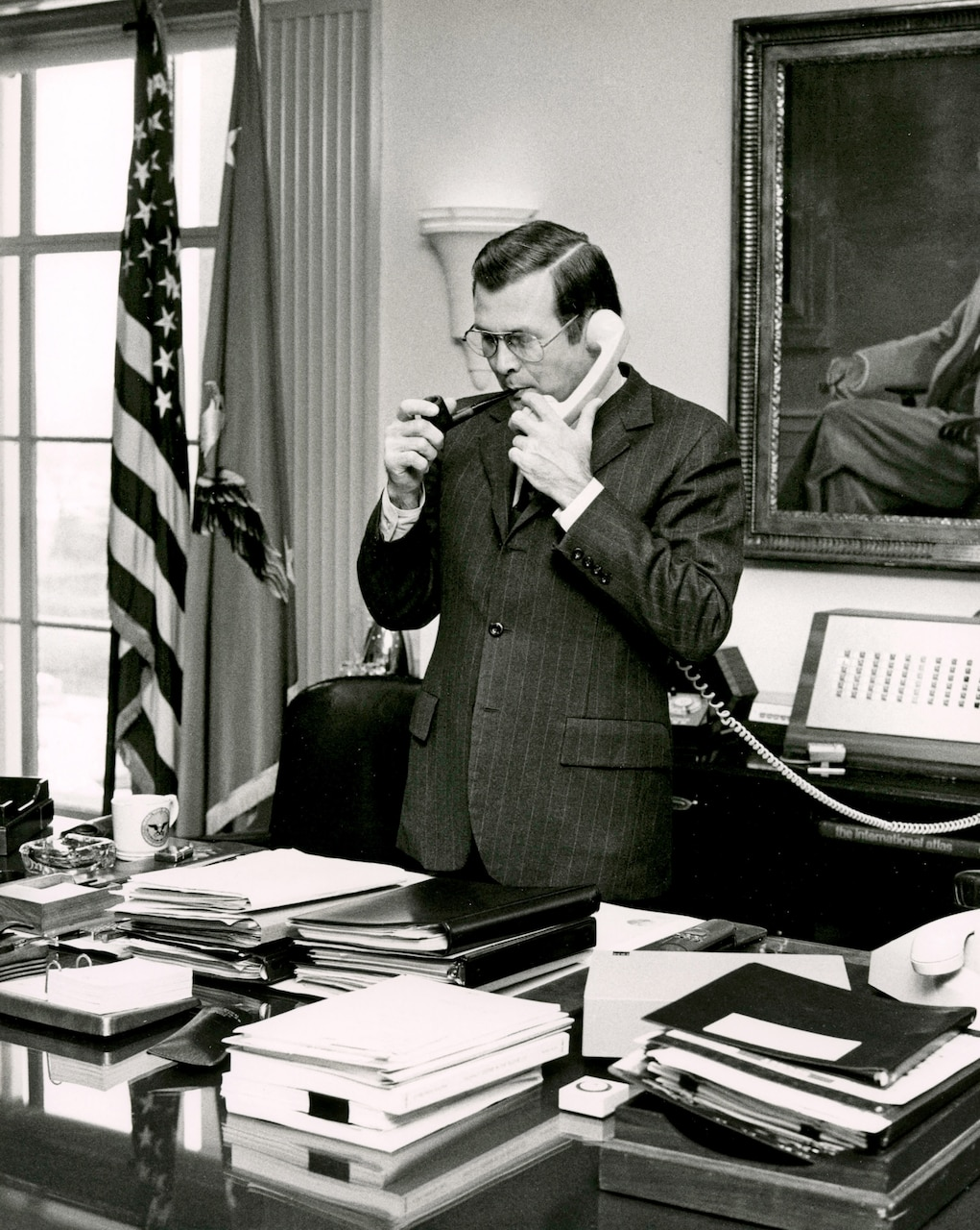 Defense Secretary Donald H. Rumsfeld stands and smokes a pipe while holding a phone.