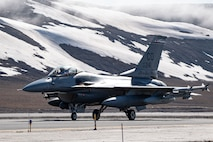 A U.S. Air Force F-16 Fighting Falcon fighter jet taxies to the ramp at Thule Air Base, Greenland, during Exercise Amalgam Dart, June 12, 2021.