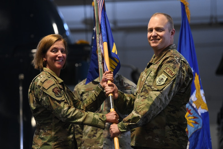 Col. Catherine Barrington, Commander of the 90th Missile Wing, passes the guidon to Col. Michael Power, the incoming commander of the 90th Maintenance Group, during the 90 MXG Change of Command Ceremony on F.E. Warren Air Force Base, Wyoming, on June 30, 2021. The change of command ceremony signifies the transition of command from Col. Brian Rico, the outgoing commander of 90 MXG, to Power. (U.S. Air Force photo by Airman 1st Class Frazier)
