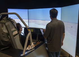 A family member tries out an F-22 Raptor flight simulator during the 412th Electronic Warfare Group Family Day at Edwards Air Force Base, California, June 18. (Air Force photo by Kyle Brasier)