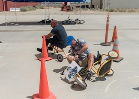 Col. Jay Orson, 412th Electronic Warfare Group commander, wipes out as Col. Randel Gordon, 412th Test Wing vice commander, goes for the win during a tricycle obstacle course race at the 412th EWG Family Day at Edwards Air Force Base, June 18. (Air Force photo by Bryce Bennett)