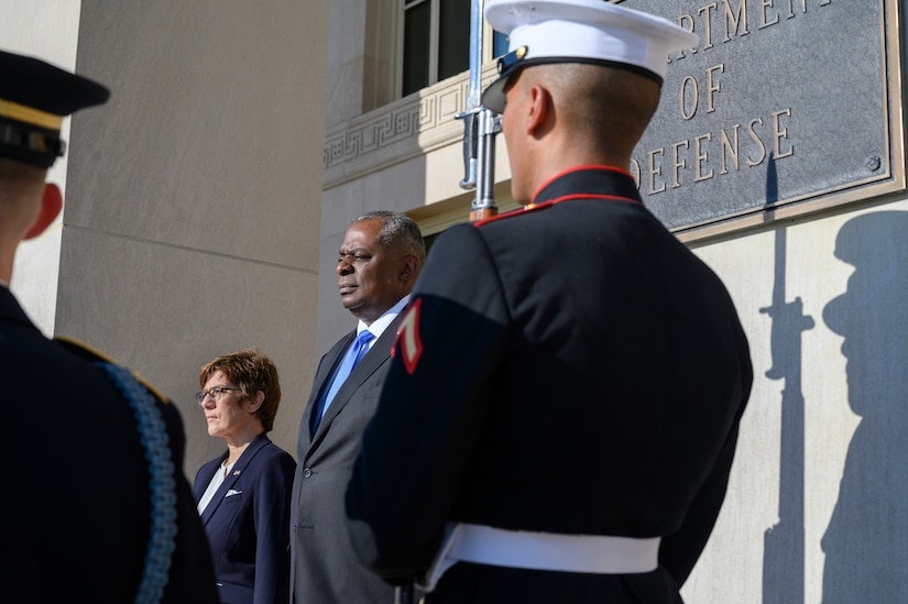 A man and a woman flanked by uniformed service members stand at the entrance of the Pentagon.