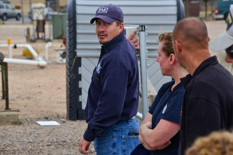 Man explains the emergency stop button to a small group of people at Kirtland, AFB.