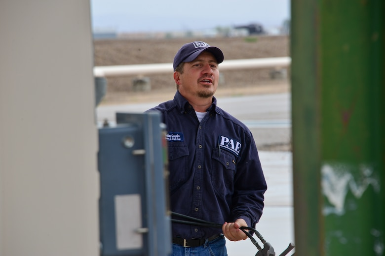 Man holds a fuel pump handles at Kirtland, AFB.