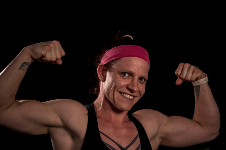 A woman wearing a work out top flexes her arms for the camera with a big smile on her face.