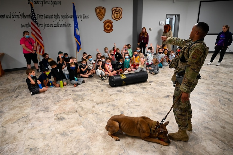 Staff Sgt. Ronald Dyer, a 28th Security Forces Squadron military working dog handler, answers questions about his partner, Lezer, from students of the Ellsworth School Age Care program during a field trip at Ellsworth Air Force Base, S.D., June 25, 2021.