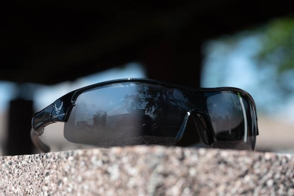 Sunglasses sit on a wall