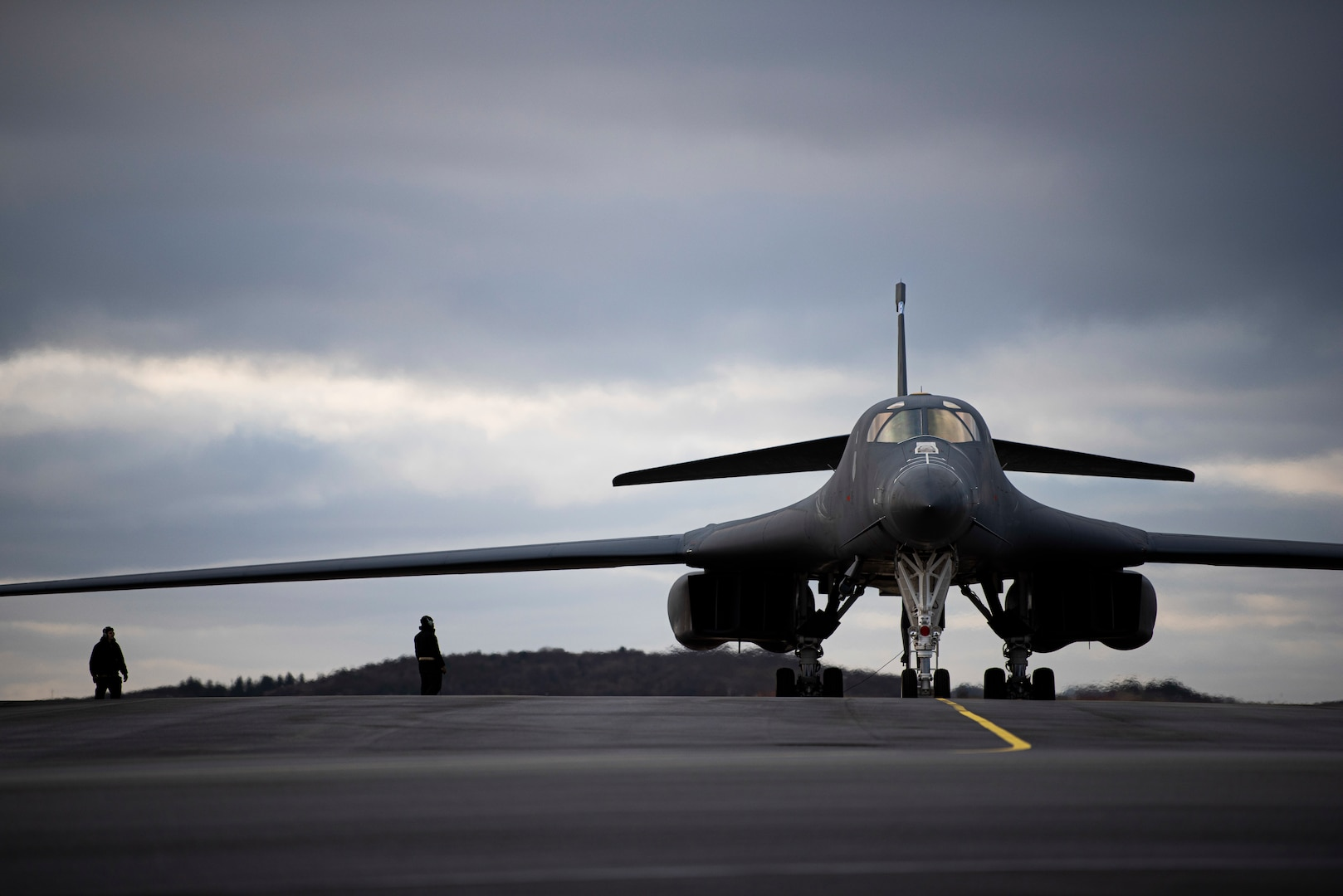 Two crew chiefs assigned to the 9th Aircraft Maintenance Unit stand by a B-1B Lancer on the flightline at Ørland Air Force Station, Norway, Feb. 26, 2021. B-1 crew chiefs provide aircraft maintenance necessary to ensure Bomber Task Force mission success. (U.S. Air Force photo by Airman 1st Class Colin Hollowell)