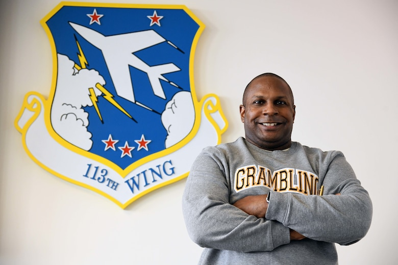 Lt. Col. Byron Coward, director of inspections with the Inspector General's Office, 113th Wing, D.C. Air National Guard, stands in front of 113th Wing emblem, Joint Base Andrews, Md., Feb. 26, 2021.