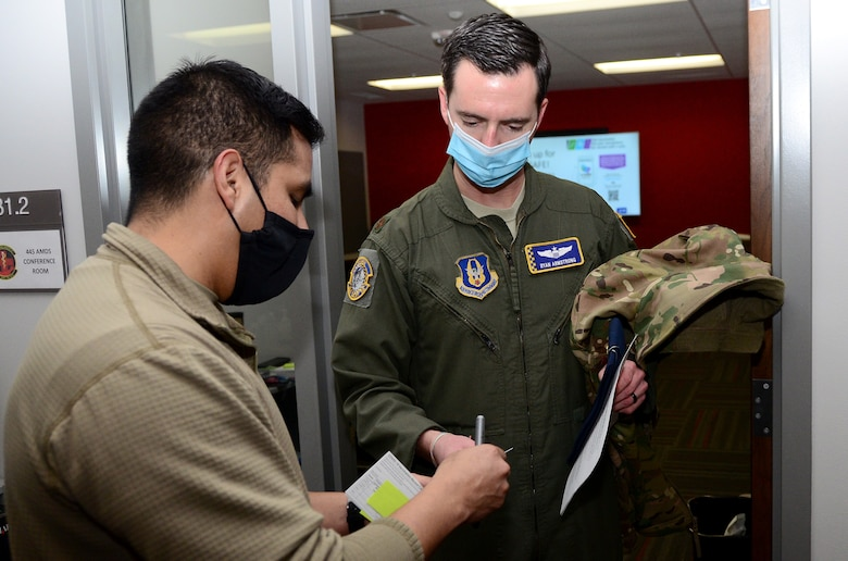Master Sgt. Christian De La Cruz, 445th Aerospace Medicine Squadron aerospace medical technician, gives Maj. Ryan Armstrong, 89th Airlift Squadron C-17 pilot, a COVID-19 vaccination record card Feb. 26, 2021. De La Cruz also provided a sticky note with the time the vaccine was administered for evaluation purposes. AMDS staff members monitored each Airman for development of side effects. The two-dose vaccine was recently approved by the Food and Drug Administration under an emergency use authorization and are currently offered to Defense Department personnel on a voluntary basis. (U.S. Air Force photo/Mr. Darrell Sydnor)
